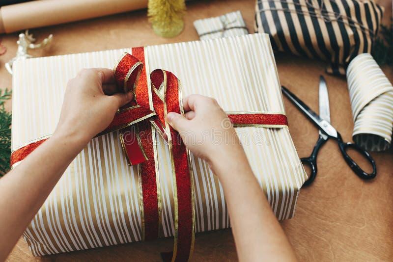 Hände mit rotem Band und verpacken stilvolle Geschenkschachtel in gestreiftem goldenen Papier und Schere, Geschenke, goldener Bau stockfoto