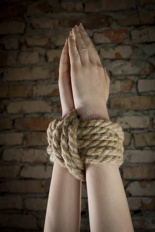 Hände oben gebunden mit Seil stockbild