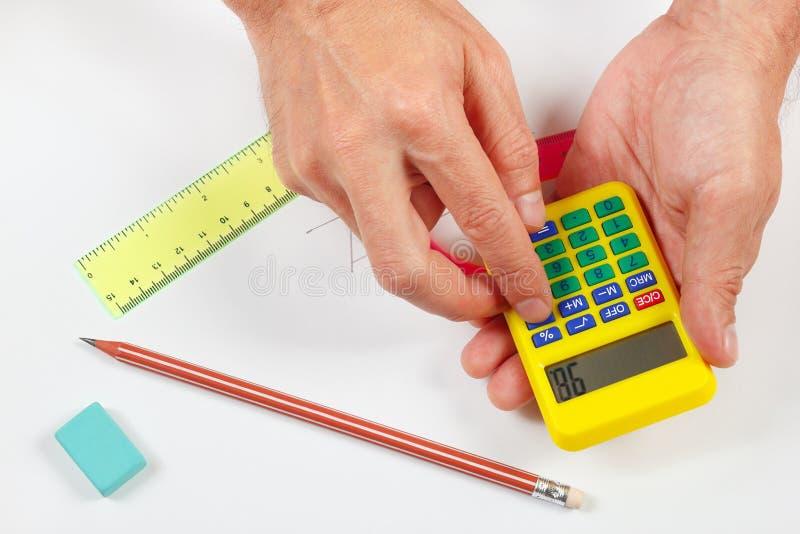 Hände rechnen unter Verwendung eines digitalen Taschenrechners über Arbeitsplatz des Ingenieurs lizenzfreie stockfotografie