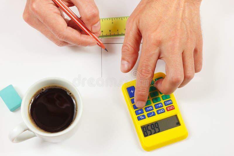 Hände rechnen unter Verwendung eines digitalen Taschenrechners der Tasche über Arbeitsplatz des Ingenieurs stockfoto