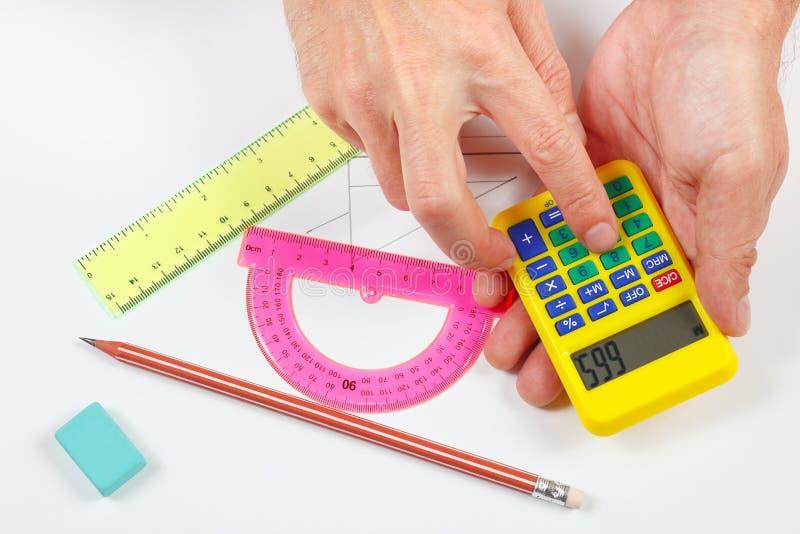 Hände rechnen unter Verwendung eines Taschenrechners über einem Arbeitsplatz des Ingenieurs lizenzfreie stockfotografie