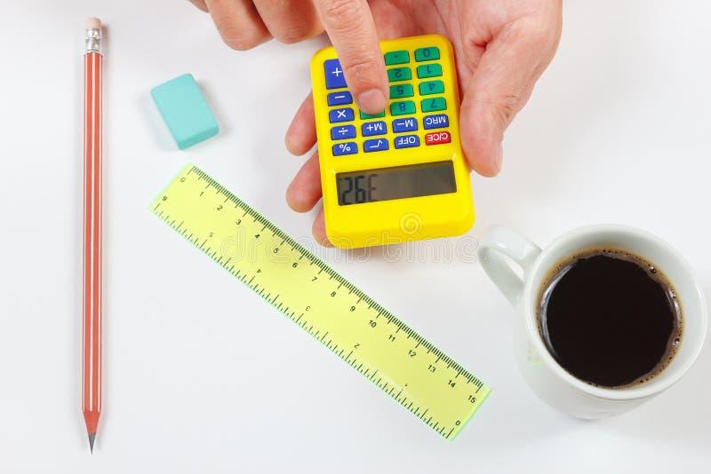 Hände rechnen unter Verwendung eines Taschenrechners über einem Arbeitsplatz des Ingenieurs lizenzfreies stockfoto