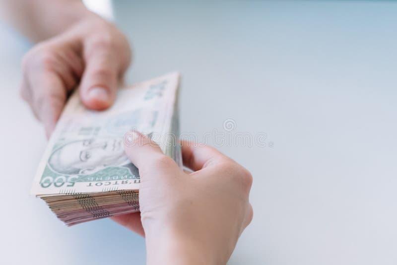 Hände rollen GeldBarzahlungs-Bestechung hryvnia zusammen stockfotografie