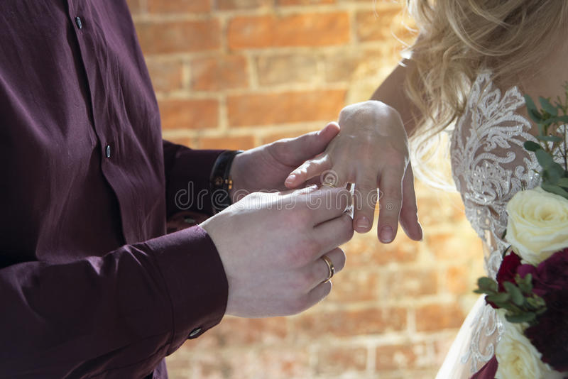 Hände schließen herauf, wenn Bräutigam den Ring auf die Braut setzt stockbild