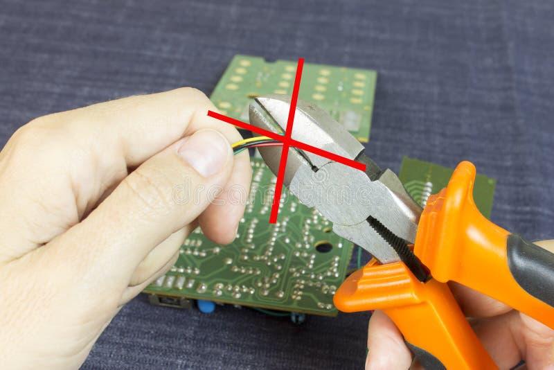 Hände schneidet Drähte mit Drahtzangen, Chip im Hintergrund stockfotografie