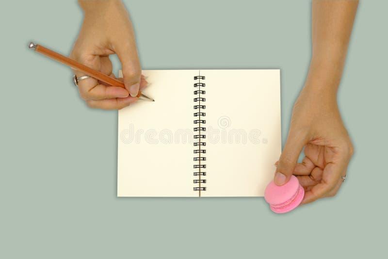 Hände schreiben auf das Buch, das auf grünem Hintergrund lokalisiert wird lizenzfreie stockfotos