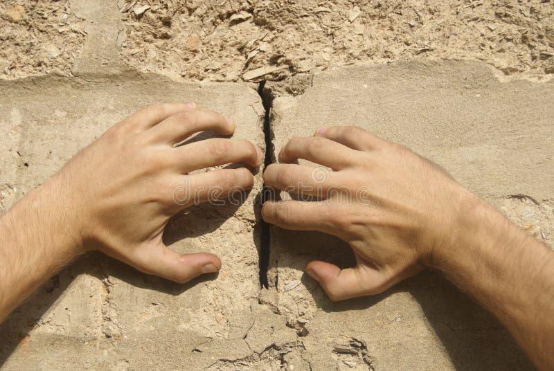Hände trennen eine Wand lizenzfreie stockfotografie