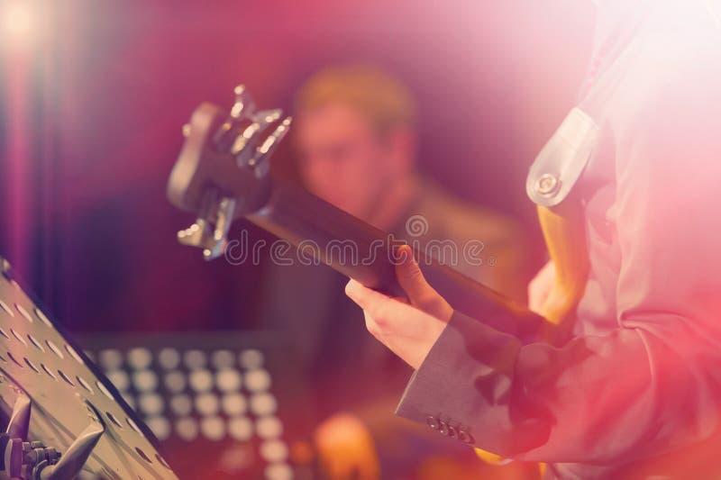 Hände und Finger des Gitarristen auf der fretboard Nahaufnahme lizenzfreie stockbilder