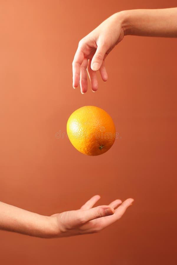 Hände und Orange lizenzfreie stockbilder