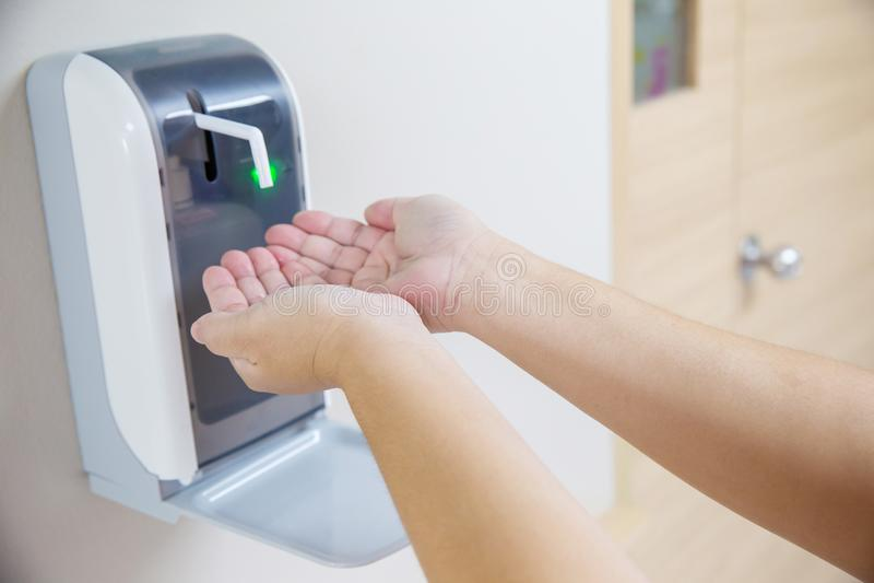 2 Hände unter der automatischen Alkoholzufuhr lizenzfreie stockfotos
