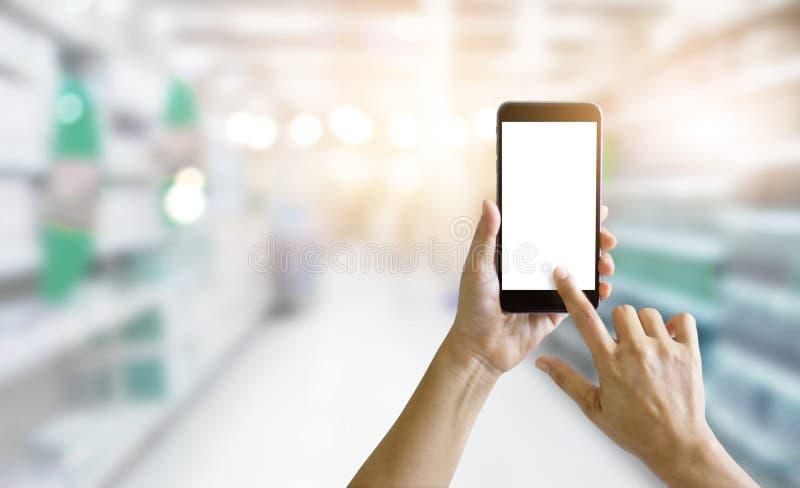 Hände unter Verwendung des intelligenten Telefons im Supermarkt für den Einkauf stockfotografie