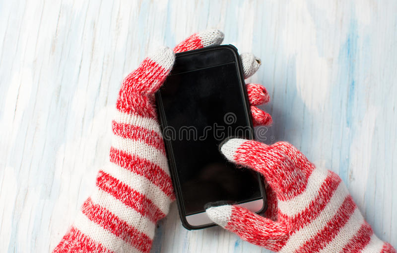 Hände unter Verwendung des Telefons in den Winterhandschuhen stockbilder