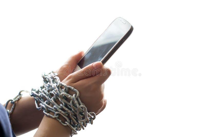 Hände verkettet durch eine Kette, die einen Handy lokalisiert auf weißem Hintergrund hält stockfoto
