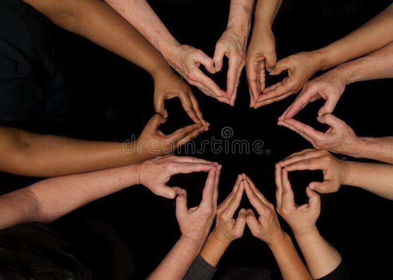 Hände von den Verschiedenartigkeitsfrauen, die kooperativ Hände in den Herzen bearbeiten stockfotos