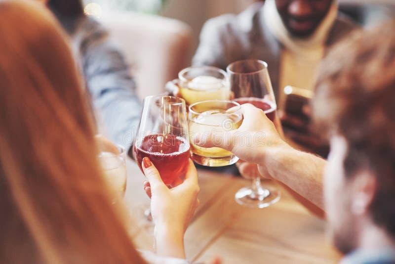 Hände von Leuten mit den Gläsern Whisky oder Wein, feiernd und rösten zu Ehren der Hochzeit oder anderer Feier stockfotografie