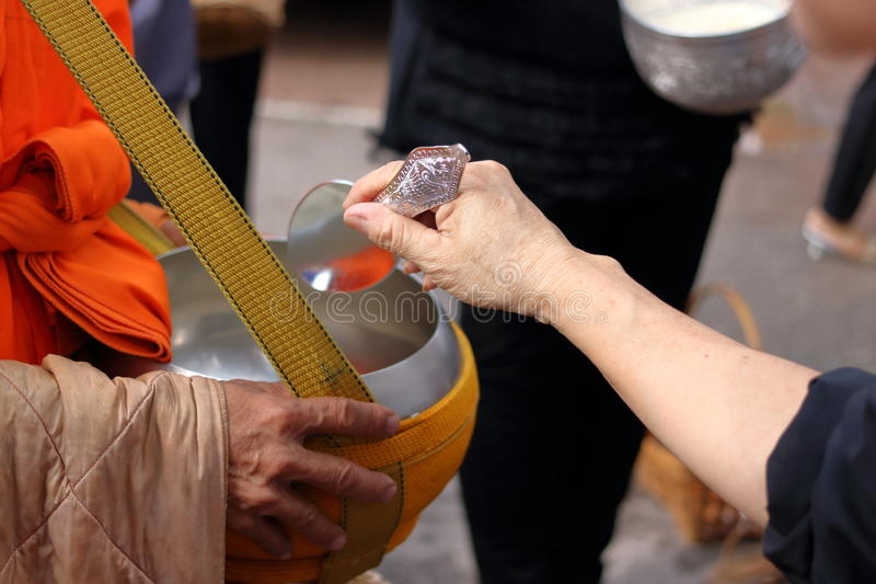 Hände von Leuten während gesetztes Lebensmittel zu einem buddhistischen monk& x27; s-Almosen rollen am Ende von buddhistischem Le lizenzfreies stockbild