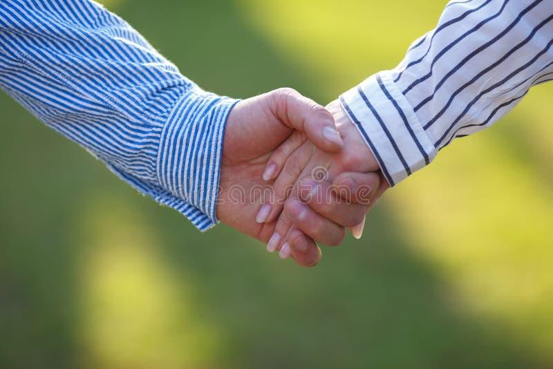Hände von liebevollen Paaren am grünen Naturhintergrund, Kopienraum L lizenzfreies stockbild
