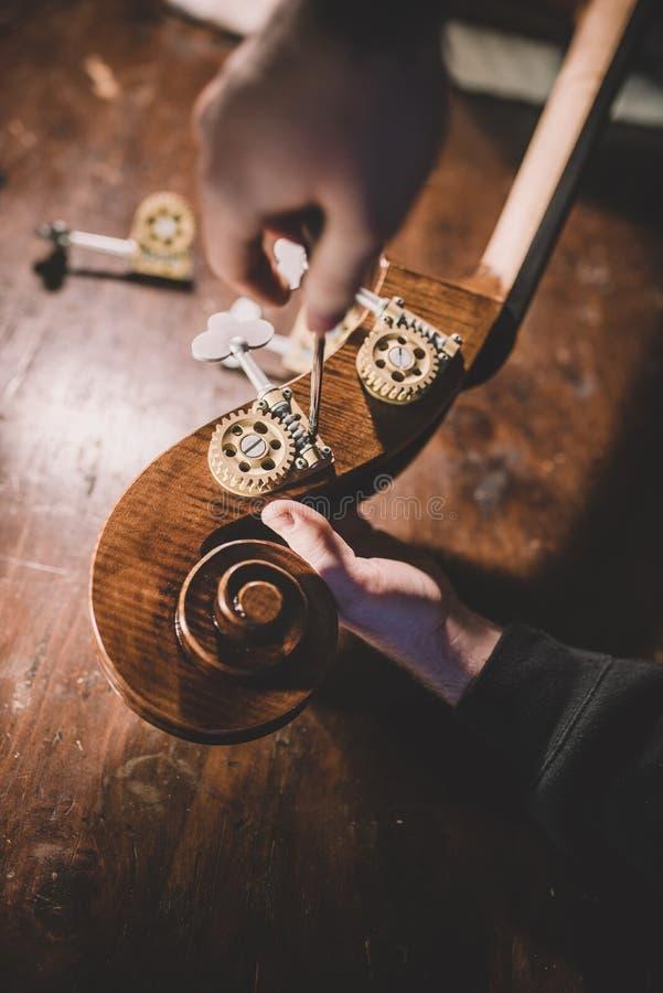Hände von luthier Lackierung des Handwerkers, einen Kontrabass errichtend stockfotografie