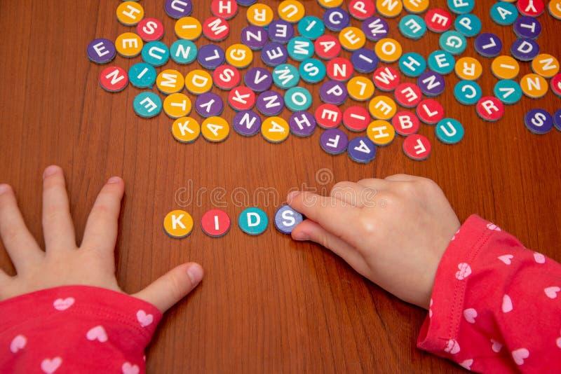 Hände von Mädchen auf einem Holztisch fügen ein Puzzlespiel von farbigen Buchstaben, hinzufügen ein Wort von farbigen Buchstaben, stockbilder