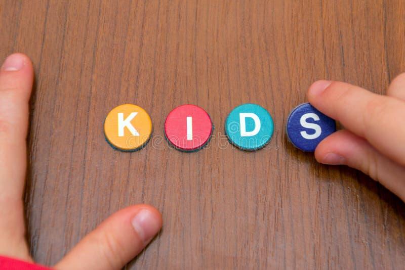 Hände von Mädchen auf einem Holztisch fügen ein Puzzlespiel von farbigen Buchstaben, hinzufügen ein Wort von farbigen Buchstaben, lizenzfreies stockfoto