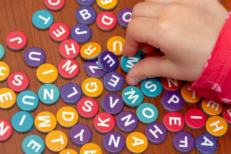 Hände von Mädchen auf einem Holztisch fügen ein Puzzlespiel von farbigen Buchstaben, hinzufügen ein Wort von farbigen Buchstaben, stockfotos