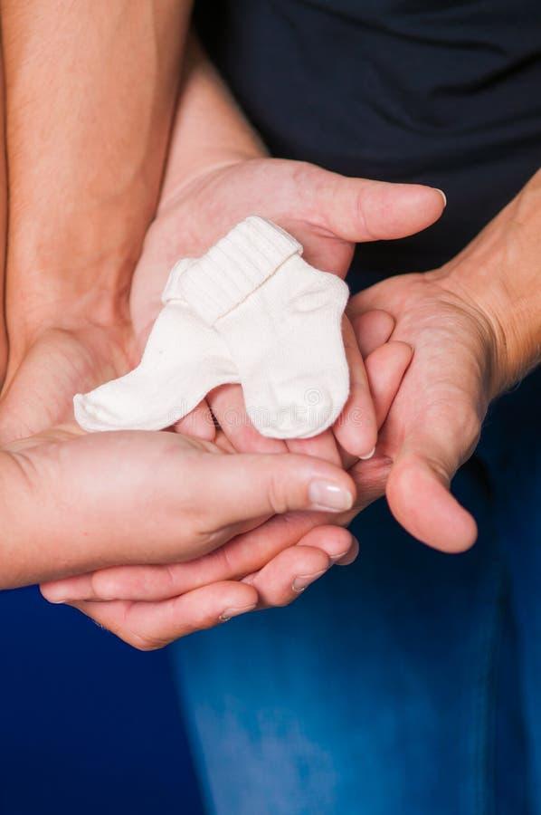 Hände von Männern und von Frauen auf schwangerem Bauch mit Socken lizenzfreie stockfotos