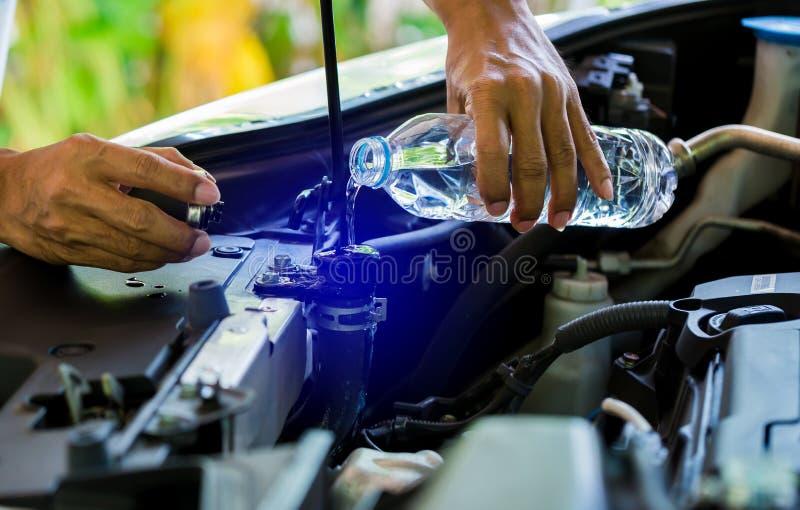 Hände von Mechaniker-Check-Wasser im Autoheizkörper und Wasser Autoheizkörper hinzufügen lizenzfreies stockfoto