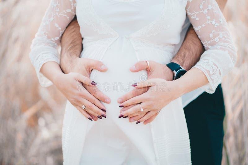 Hände von zukünftigen Eltern - unerkennbarer Mann und Frau auf schwangerem Bauchhintergrund lizenzfreies stockfoto