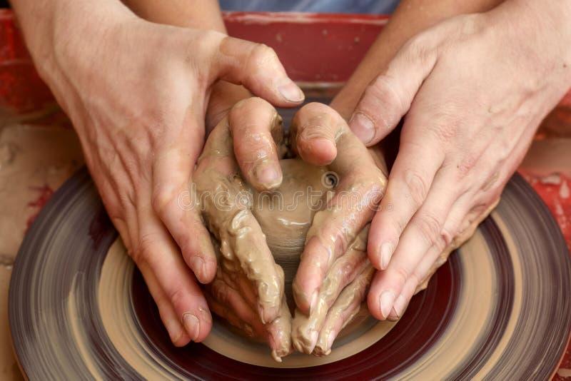 Hände von zwei Leuten stellen Topf, Töpfer ` s Rad her Unterrichtende Tonwaren stockfoto