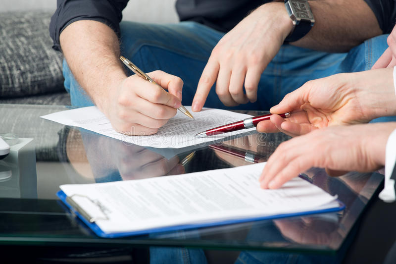 Zwei Leute, die ein Dokument unterzeichnen stockfotografie
