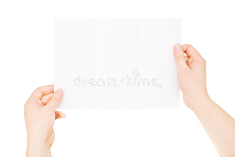 Hände, welche die dreifachgefaltete leere Broschüre, etwas gefaltet, lokalisiert halten stockfoto