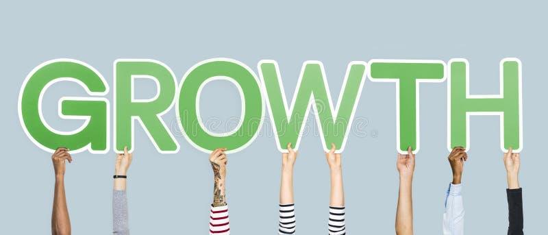 Hände, welche die grünen Buchstaben bilden das Wortwachstum halten stockfoto