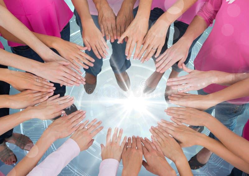 Hände zusammen im Kreis über hellem Portallicht mit rosa T-Shirts stockfotografie