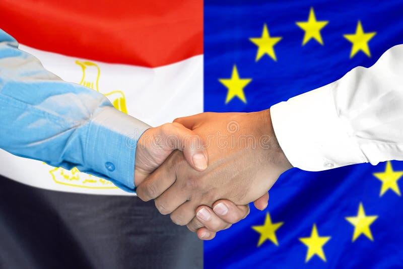 Händedruck auf Ägypten- und Gemeinschaftsflagge Hintergrund lizenzfreie stockfotos
