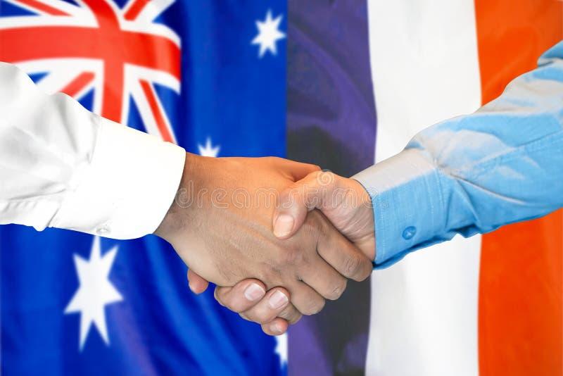 Händedruck auf Australien- und Frankreich-Flagge Hintergrund stockfotografie