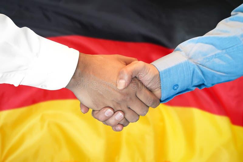 Händedruck auf Deutschland-Flaggenhintergrund stockbild