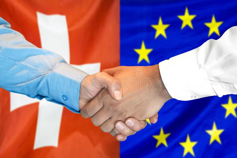 Händedruck auf Schweiz- und Gemeinschaftsflagge Hintergrund lizenzfreies stockbild