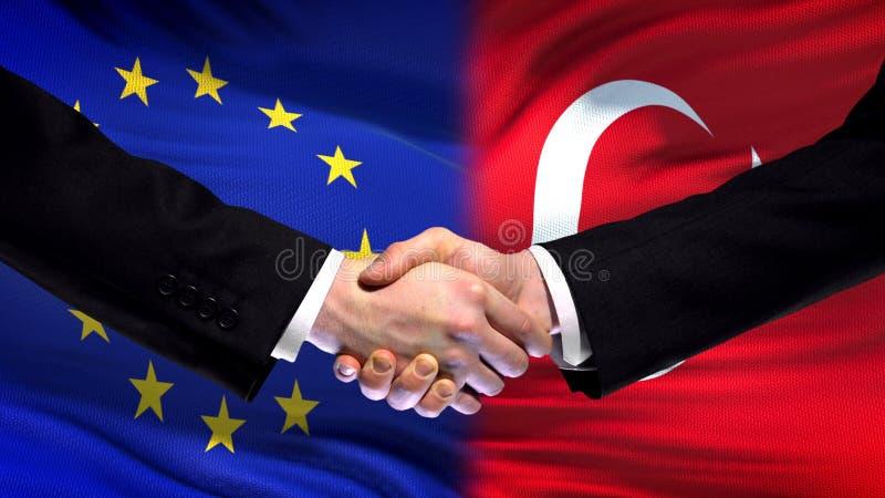 Händedruck der Europäischen Gemeinschaft und der Türkei, internationale Freundschaft, Flaggenhintergrund lizenzfreies stockbild