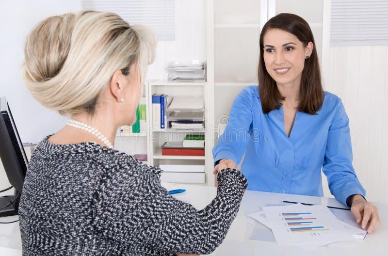 Händedruck: Lächelnde Geschäftsfrau zwei im Büro lizenzfreie stockfotografie