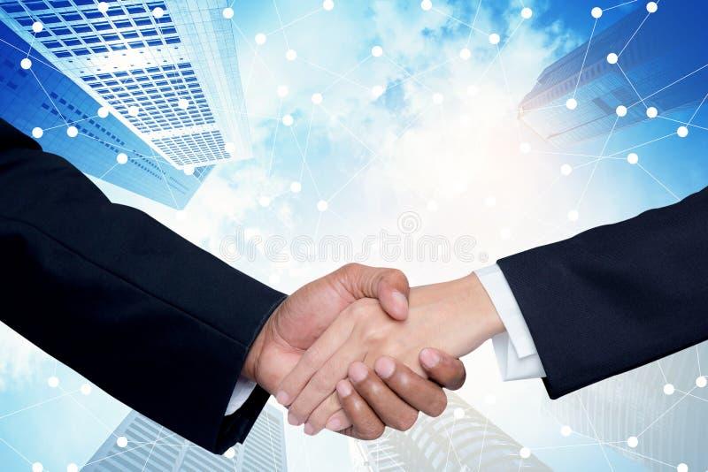 Händedruck zwischen einem Geschäftsmann und einer Geschäftsfrau mit Gebäudestadthintergrund lizenzfreie stockfotos