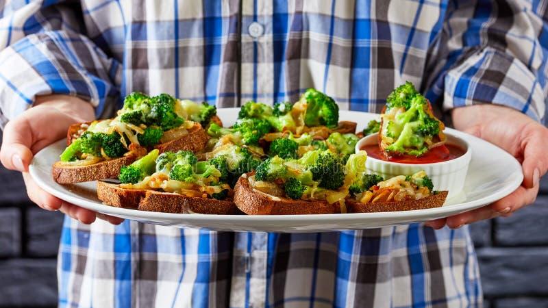Händen von Frauen, die einen Teller mit Brokkoli schmelzen lizenzfreies stockbild