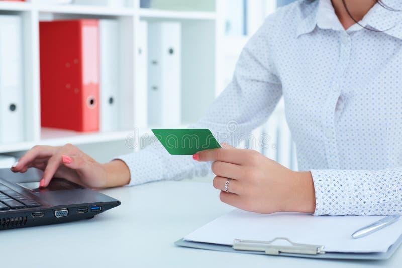 Händer av affärskvinnan i hållande kreditkort för dräkt och danandeonline-köp genom att använda anteckningsbokPC arkivfoto