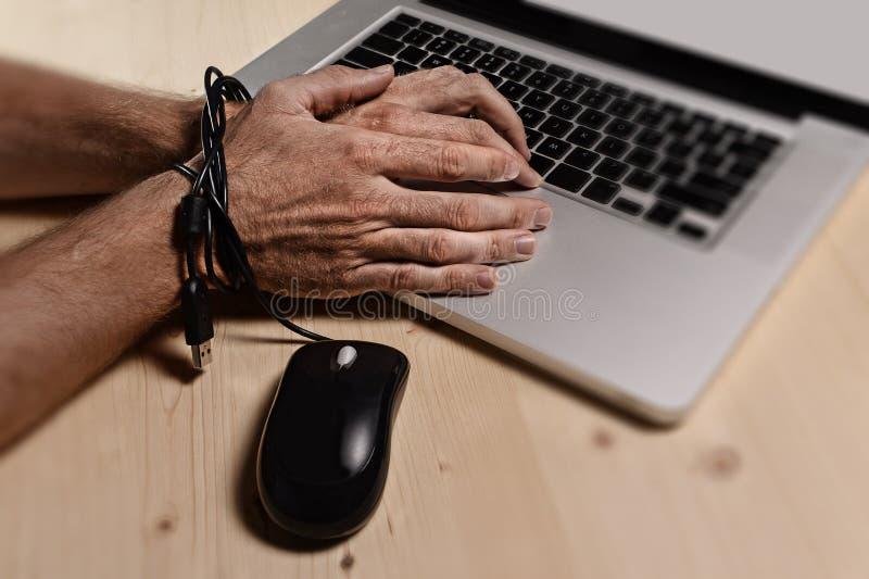 Händer av affärsmannen missbrukade för att arbeta förbindelsen med muskabel till datorbärbara datorn i arbetsnarkoman arkivbild