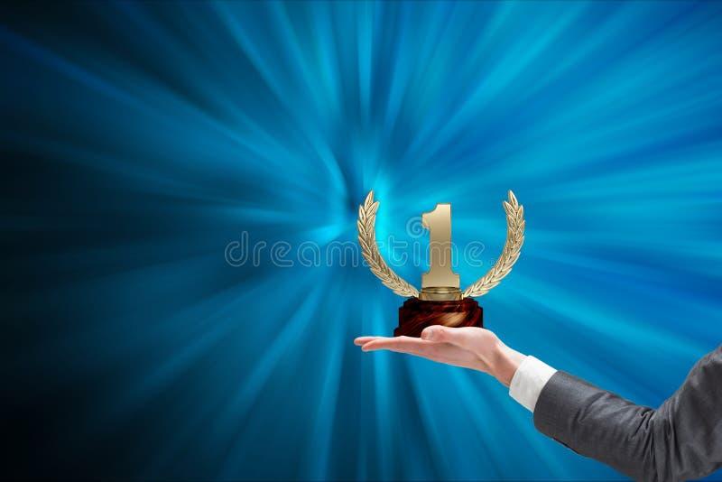 Händer av affärsmannen som rymmer en trofé i en blå bakgrund royaltyfria bilder