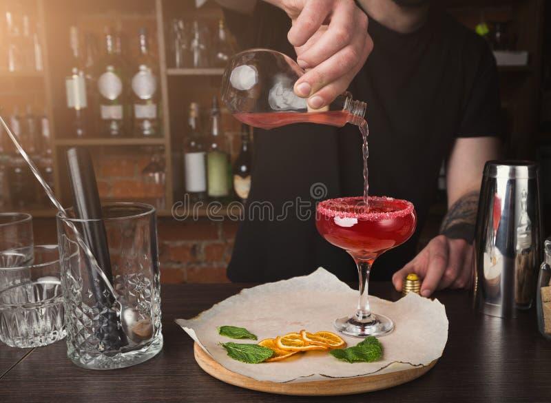 Händer av bartendern som förbereder coctailen på stångräknaren arkivbilder