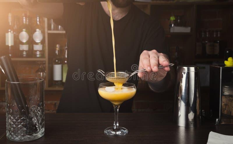 Händer av bartendern som förbereder coctailen på stångräknaren arkivfoto