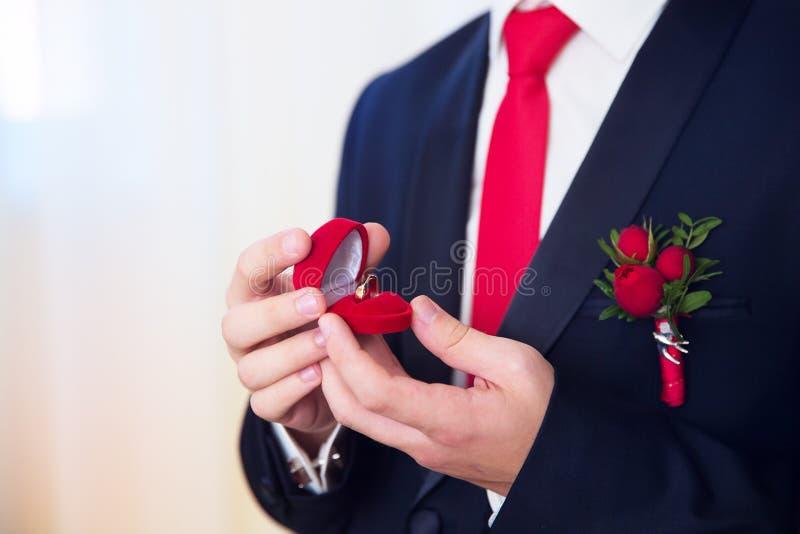 Händer av bröllopbrudgummen som får klara i dräkt Brudgummen rymmer th royaltyfri bild