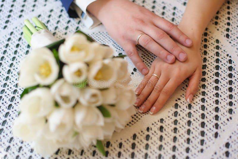 Händer av brud- och brudgumnärbilden på tabellen royaltyfri bild