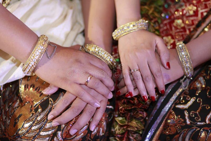 Händer av brud- par i Javanesebröllop royaltyfria bilder
