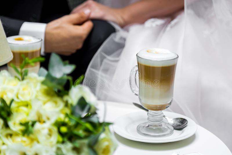 Händer av bruden och brudgummen för en kopp kaffe Bröllopbukett på bordlägga royaltyfria foton